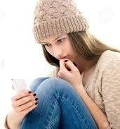 teen looking at smartphone has sad expression